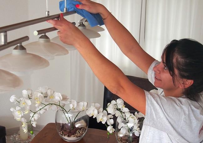 Wohnungsreinigung: Putzfrau beim Staubwischen
